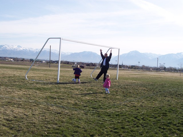 Emma, Sarah, and Dad playing soccer