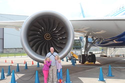 Sarah, Steve, and Emma in front of the engine of a 787
